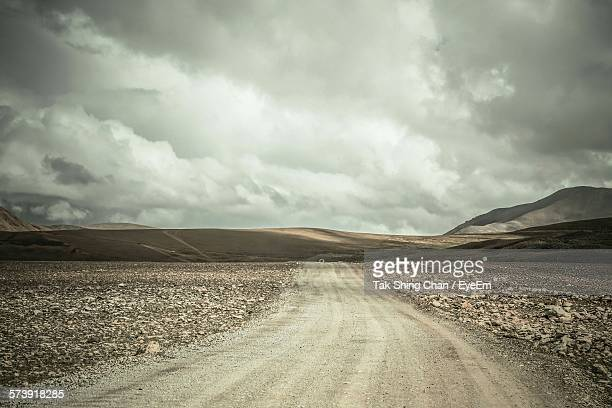 Dirt Road Amidst Field Against Cloudy Sky
