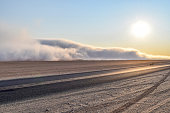 abandoned area with dusty dirt road and some fog at evening time in Namibia, Africa
