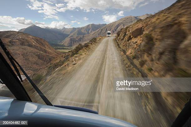 Dirt road near Urubamba City, bus approaching, view through windscreen