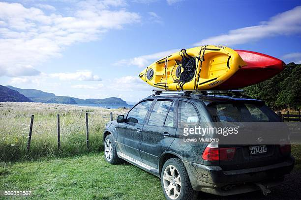 A dirty car parked on grass near beach with two sea kayaks on roof Coromandel New Zealand North Island