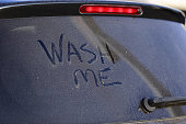 Dirty car window and wash me sign