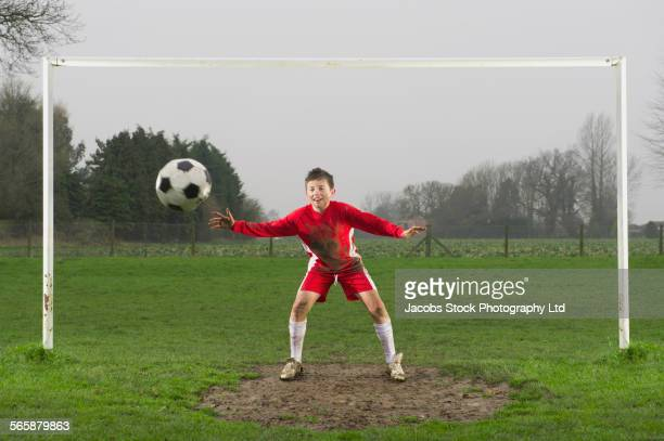 Dirty Caucasian boy guarding goal in soccer field
