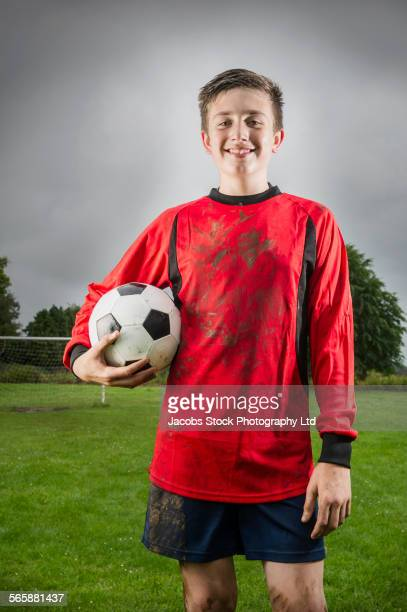 Dirty Caucasian soccer player holding ball on field