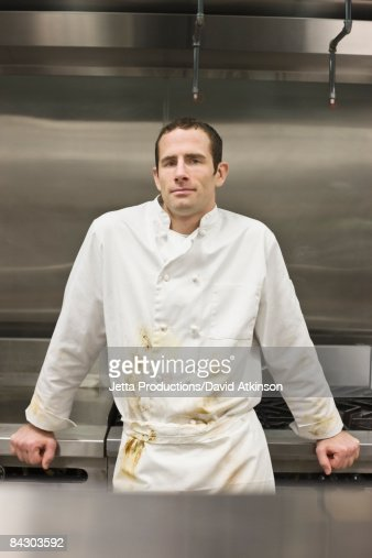 Dirty chef leaning against stove
