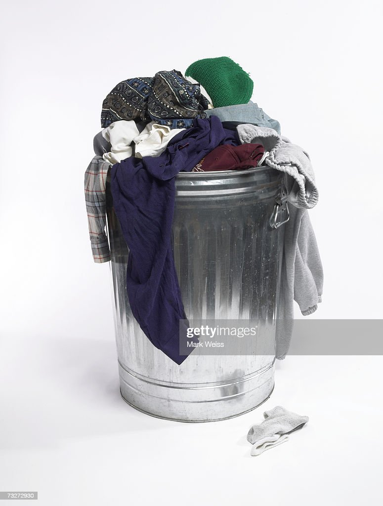 Dirty clothes in trash can : Stock Photo