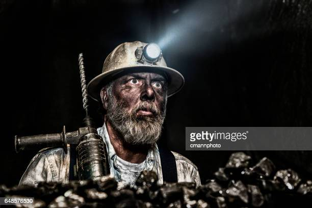 Dirty coal miner wear hardhat with a hammer drill