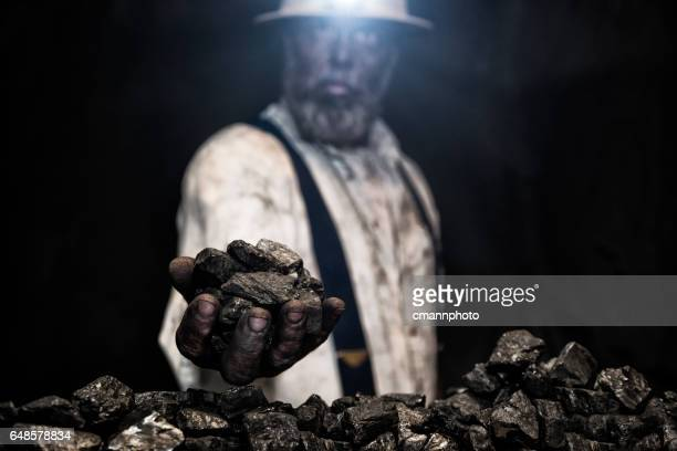 Dirty coal miner wear hardhat with handful of coal