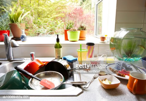 Dirty dishes piled in kitchen sink, close-up : Stock Photo