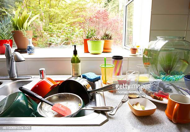 Dirty dishes piled in kitchen sink, close-up