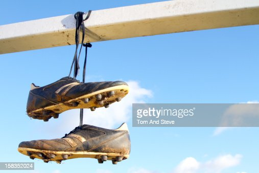 Dirty football boots hanging over a goal crossbar : Stock Photo