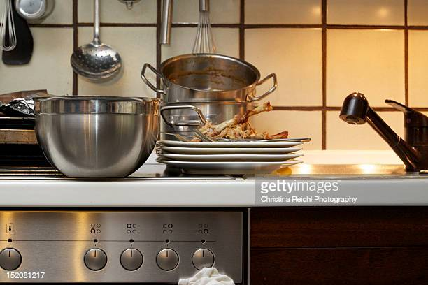 Dirty kitchen with used plates, bowl and pot