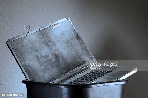 Dirty laptop in rubbish bin, studio shot