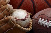 close up shot of well worn baseball in baseball glove, football and basketball