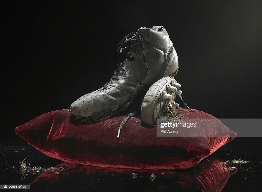 Dirty soccer shoes on velvet cushion : Stock Photo