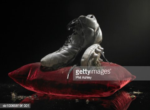 Dirty soccer shoes on velvet cushion : Stock Photo