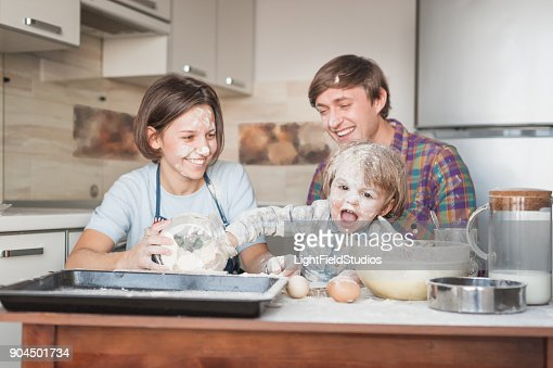 dirty young family cooking with flour together at kitchen : Stock Photo