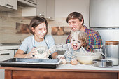 dirty young family cooking with flour together at kitchen