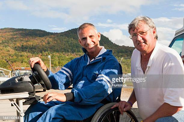 Disability racer with spinal cord injury in wheelchair at driving simulator with his coach