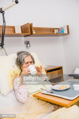 Disable Senior Woman Having Breakfast In Her Bed At The Retirement Home : Stockfoto