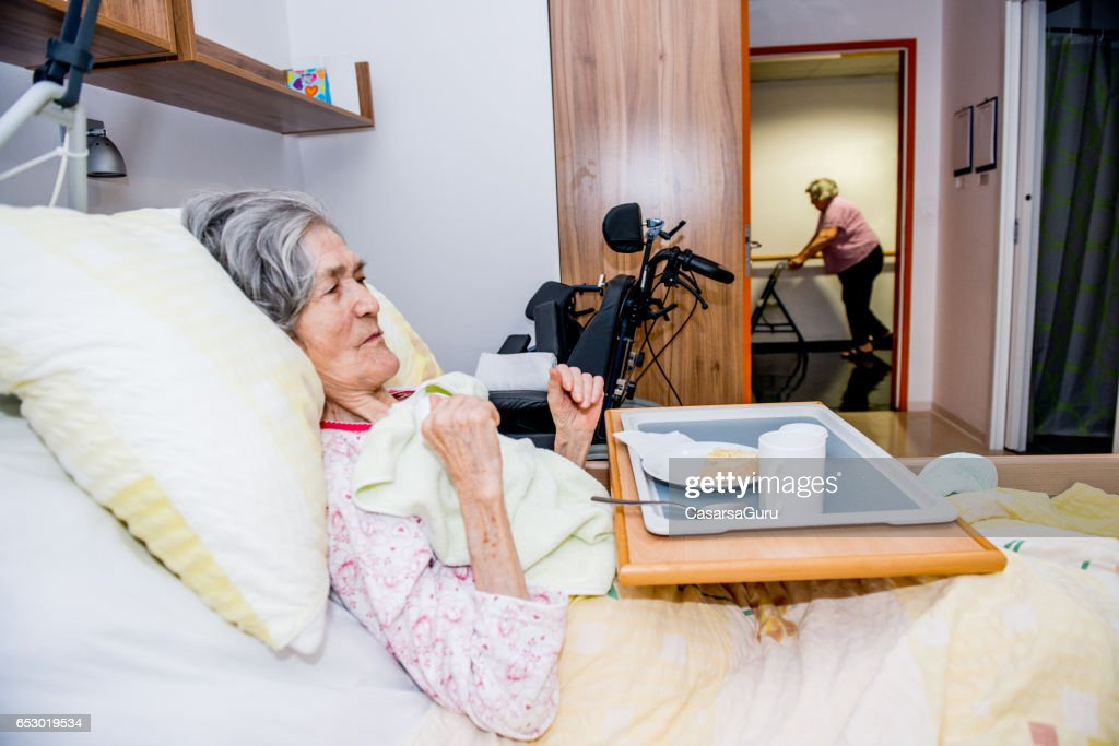 Disable Senior Woman Having Breakfast In Her Bed At The Retirement Home : Stock-Foto