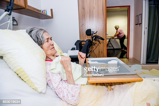 Disable Senior Woman Having Breakfast In Her Bed At The Retirement Home : ストックフォト