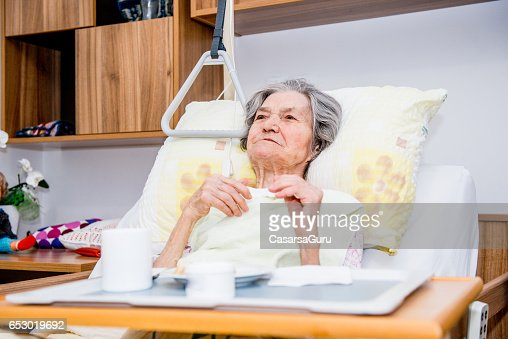 Disable Senior Woman Having Breakfast In Her Bed At The Retirement Home : Foto stock