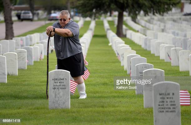 Disabled Army veteran Marcus Cook pays his respects to his father Paul also an Army veteran and his mother Adeline as well as other family members at...