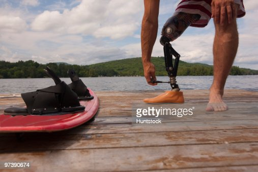 Disabled athlete adjusting his artificial leg on a dock : Stock Photo