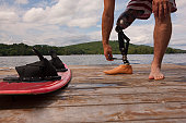 Disabled athlete adjusting his artificial leg on a dock