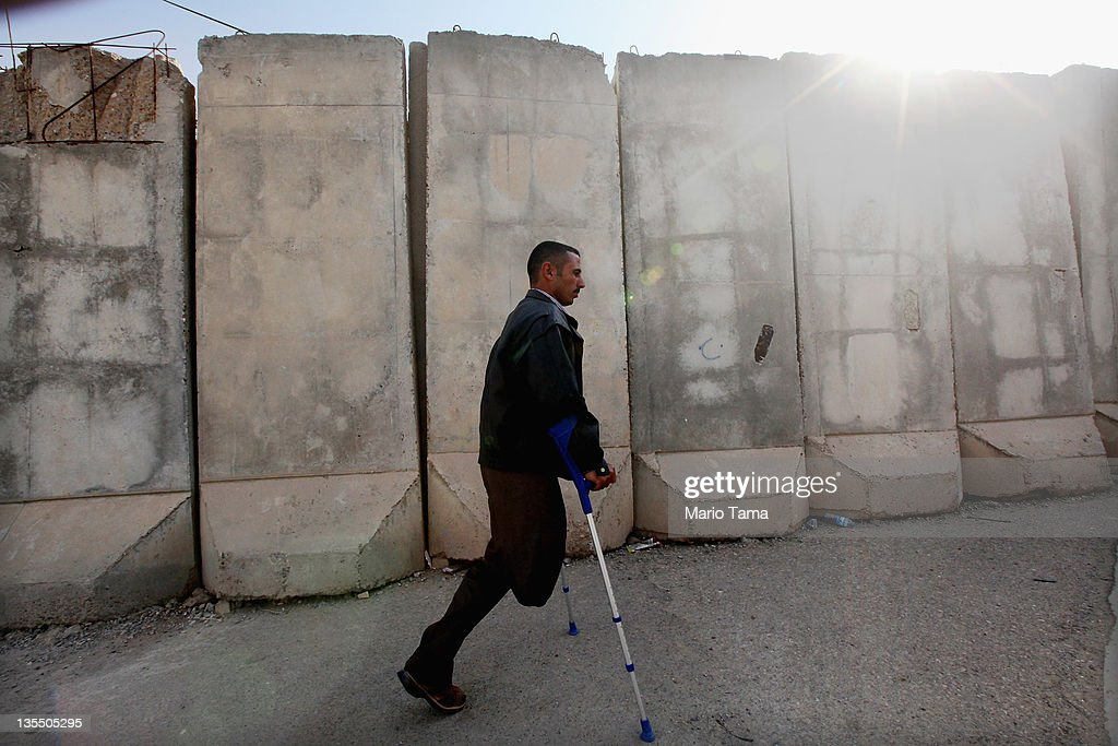 Disabled athlete Saad Hussein, who said he was wounded by an American bomb in January, 2008, walks past a blast wall through the Al Thura Disabled Veteran's Community to meet a family member who lives there on December 11, 2011 in Baghdad, Iraq. Hussein said he was farming with his cousin when the bomb struck. Iraq is transitioning nearly nine years after the 2003 U.S. invasion and subsequent occupation. American forces are now in the midst of the final stage of withdrawal from the war-torn country. At least 4,485 U.S. military personnel have died in service in Iraq. According to the Iraq Body Count, more than 100,000 Iraqi civilians have died from war-related violence.