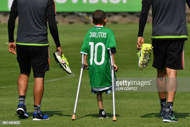 TOPSHOT A disabled boy invited by Mexico's national team footballers is escorted by defender Nestor Araujo and Jorge Hernandez during a training...