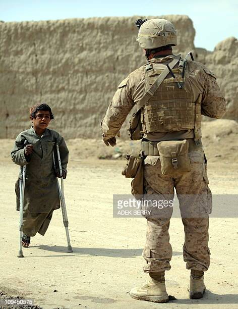 A disabled boy walks towards a US Marines 2nd Batallion 1st Marines Regiment as the take action after finding a Rocketpropelled Grenade during a...