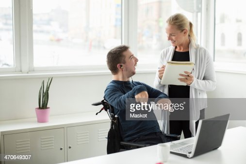 Disabled businessman discussing work with colleague in office