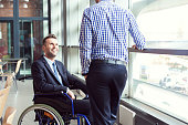Disabled businessman talking with coworker