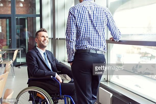 Homme d'affaires parlant à un collègue pour personnes à mobilité réduite