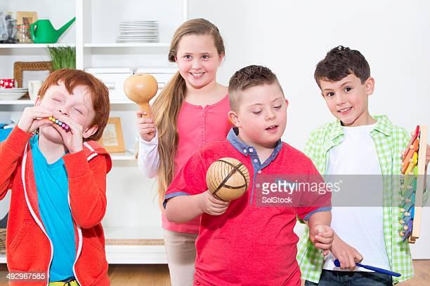 Behinderte Kinder mit Freunden spielen Musikinstrumente