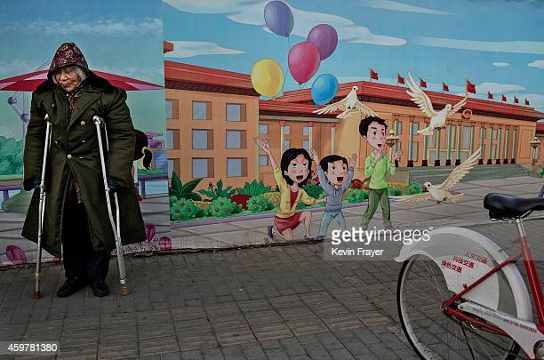 A disabled Chinese pensioner stands in the street next to a propaganda billboard showing a cartoon scene depicting the Great Hall of the People in...