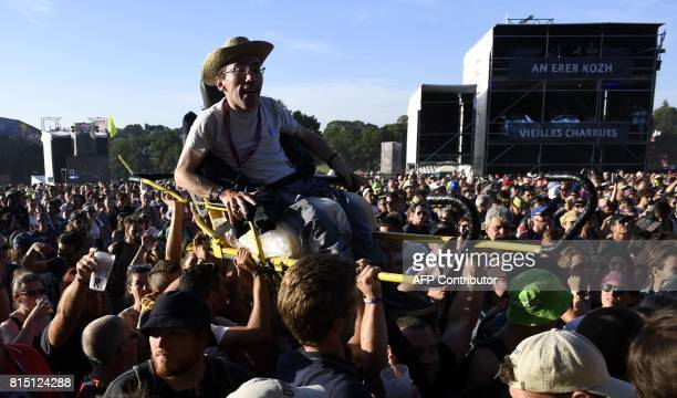 A disabled concert goer is held aloft by members of the crowd to get a better view of French rapper Kery James as he performs during the third day of...