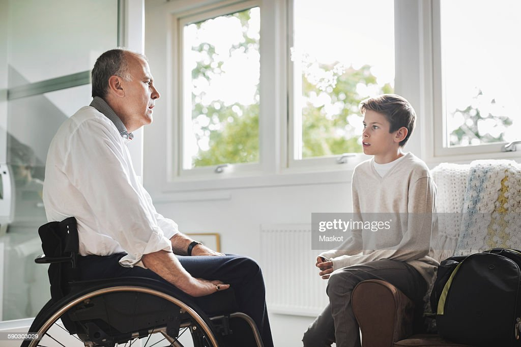 Disabled father in wheelchair talking to son at home : Photo