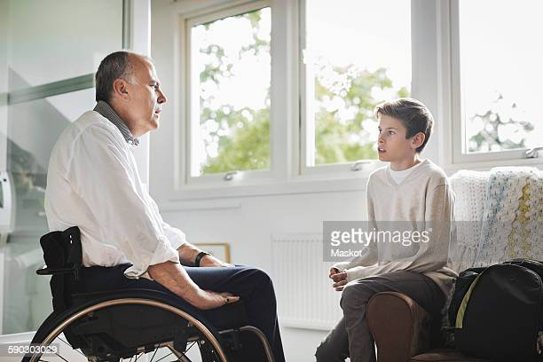 Disabled father in wheelchair talking to son at home