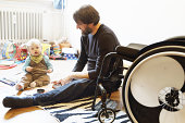 Disabled father with son playing on floor