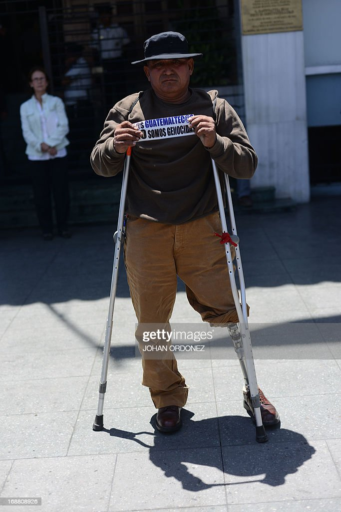 A disabled former soldier, supporter of former Guatemalan de facto President (1982-1983) retired General Jose Efrain Rios Montt, shows a sign reading 'The Guatemalans we are not genocidal' during a protest against the latter's prosecution, outside the Constitutional Court in Guatemala City on May 15, 2013. Rios Montt was found guilty of genocide and war crimes on May 10 and sentenced to 80 years in prison in a landmark ruling stemming from massacres of indigenous people in his country's long civil war. Rios Montt thus became the first Latin American convicted of trying to exterminate an entire group of people in a brief but particularly gruesome stretch of a war that started in 1960, lasted 36 years and left around 200,000 people dead or missing. AFP PHOTO / Johan ORDONEZ