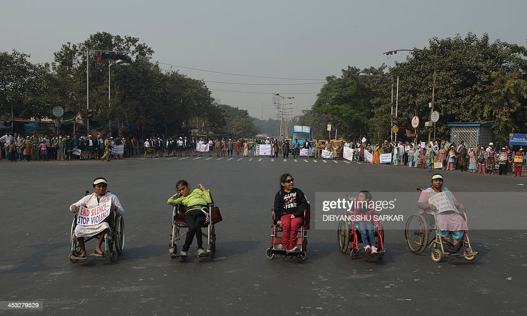 Disabled Indian children are surrounded by volunteers from the Disability Activist Forum (DAF) as they form a human chain at an event to mark International Day of People with Disability in Kolkata on December 3, 2013. According to a United Nations report on disabilities, physical, mental and sensory impairments are very common, affecting some 10 per cent of the world's population. AFP PHOTO/Dibyangshu SARKAR