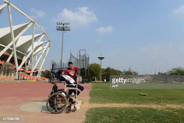 Disabled Indian sportswoman Deepa Malik is supervised by a coach while throwing a javelin during an athletics practice session at The Jawaharlal...