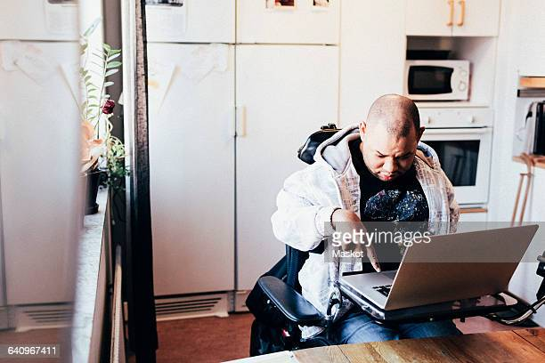 Disabled male using laptop while sitting on wheelchair at recording studio