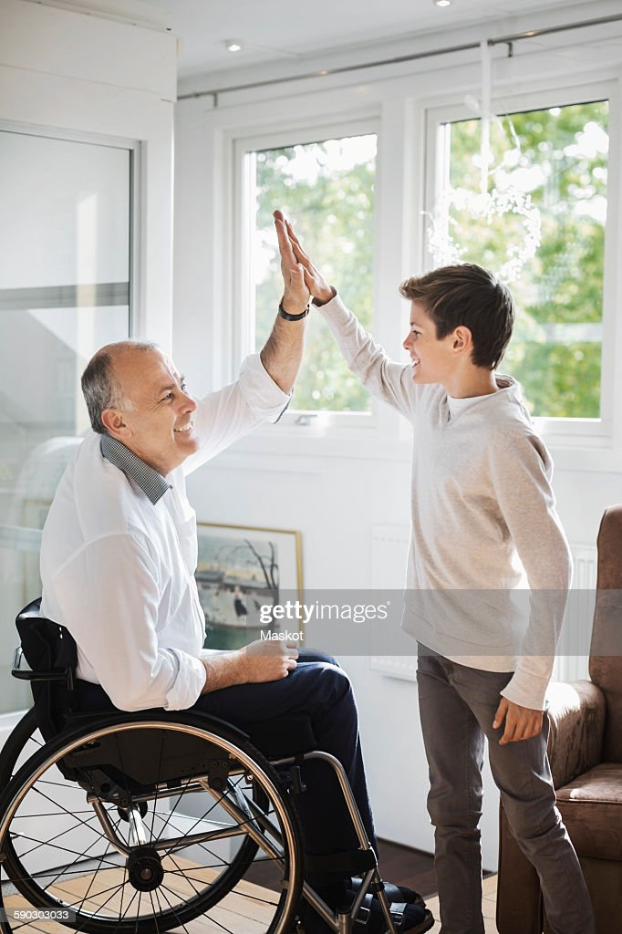 Disabled man in wheelchair giving high-five to son at home : Photo