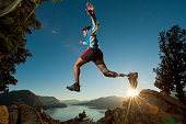 'Disabled man with prosthetic leg, jumping on a mountain with a beautiful backdrop and the sun setting.'