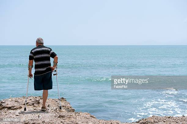 Disabled man on crutches on rocks at the sea