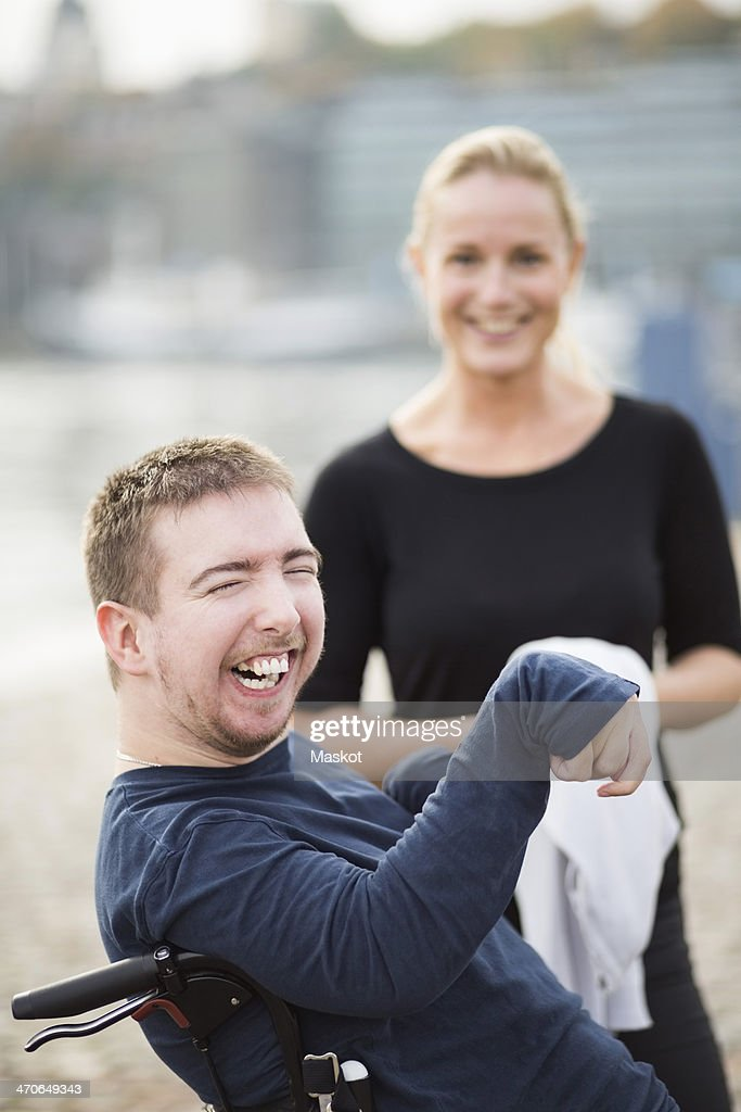 Disabled man on wheelchair laughing by caretaker outdoors