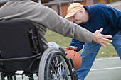 Disabled man playing basketball with his son